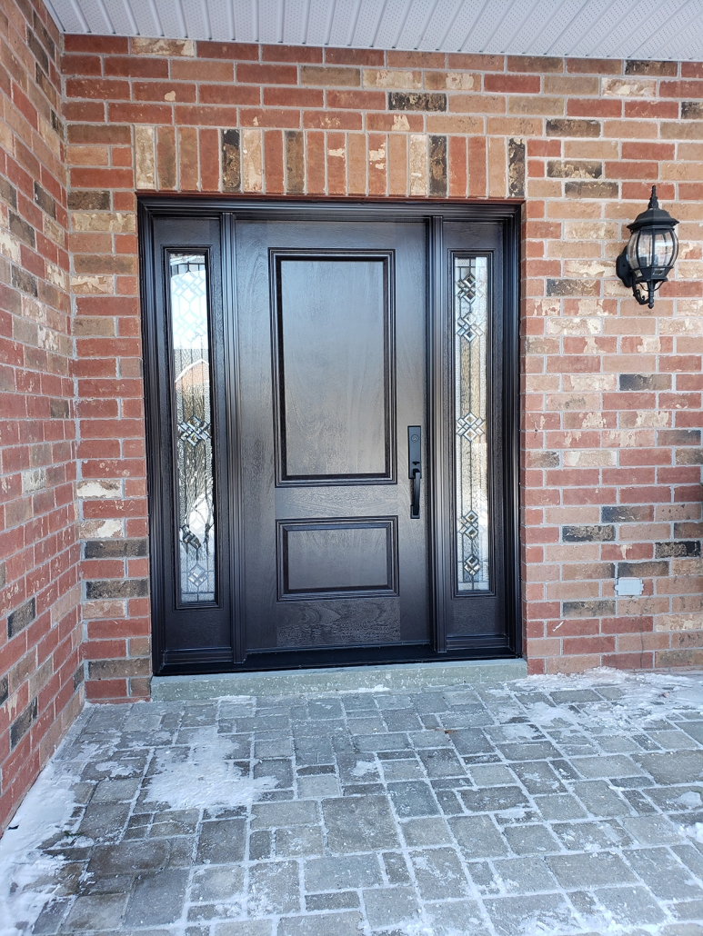 Fiberglass solid door with mahogany grained and decorative glass sidelites in Queensville
